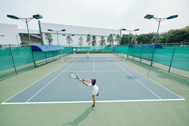 テニス選手がジャンプしてボールを打つ