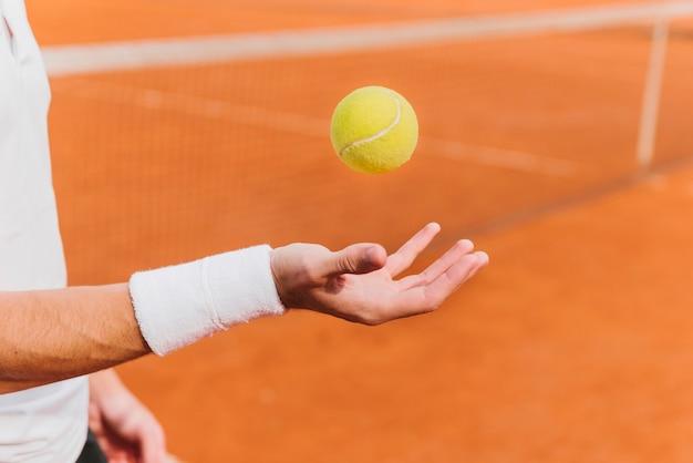 Теннисистка запускает теннисный мяч