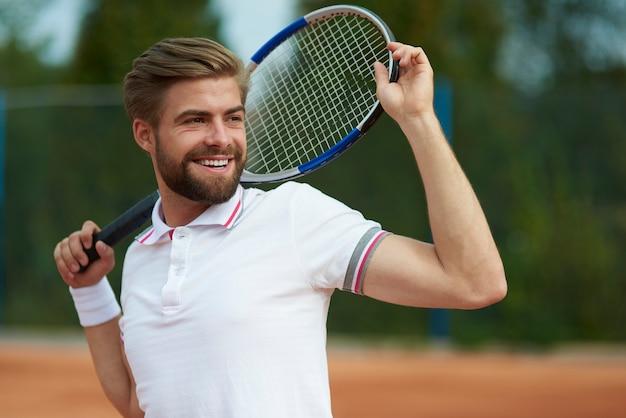 コートで目をそらしているテニス選手