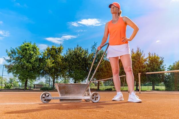 테니스 선수는 테니스 코트에 라임 화이트 라인을 표시