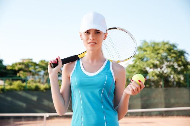 ラケットとボールを持ってコートにいるテニスプレーヤー。正面を見る