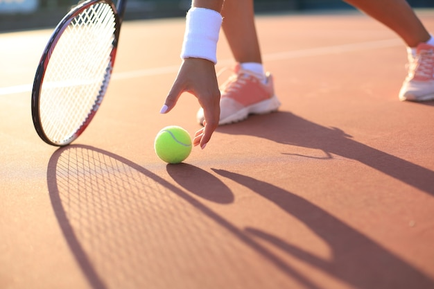 Tennis player raises a tennis ball from the clay court during the game.