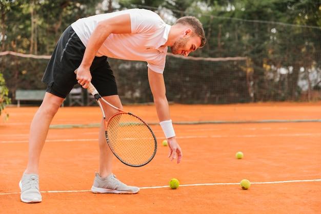 Tennis player taking a ball