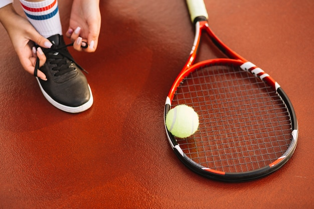 Tennis player tying shoelaces on the tennis field