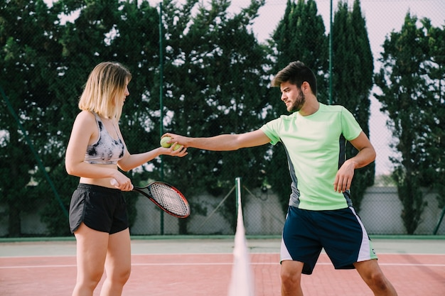 Tennis players interchanging ball
