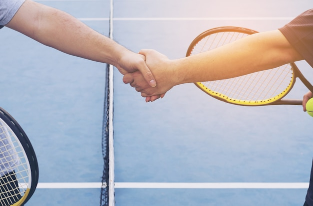 Tennis players shaking hand before match in tennis court