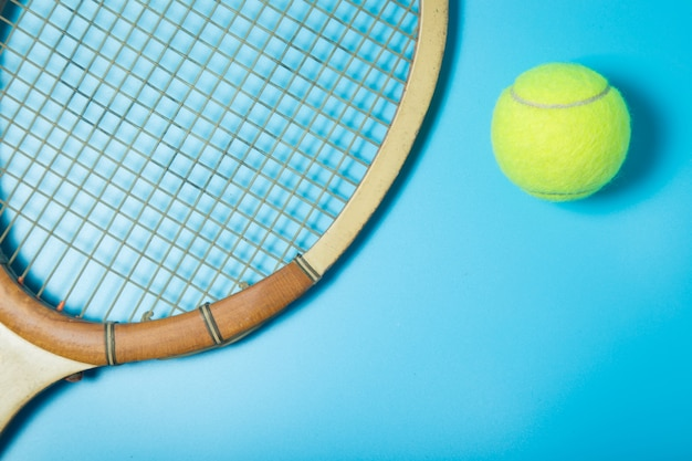 Tennis racket and ball on blue background. sport equipment. flat lay.