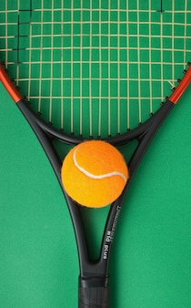 Tennis racket and  ball on a green background