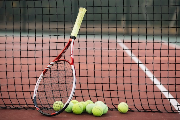Tennis racket and balls on a tennis net