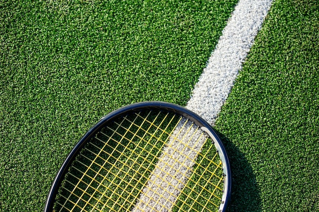 Tennis racket on a green grass court . summer sport concept. top view, free space for text .