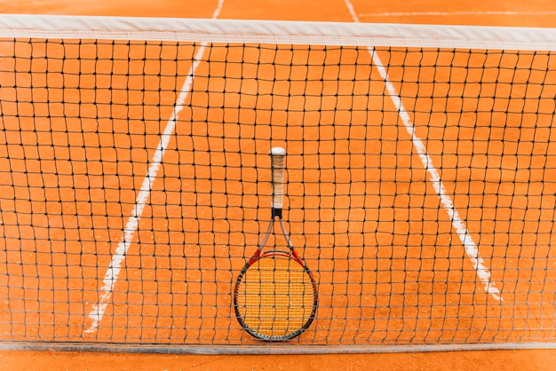 Tennis racket standing on the net