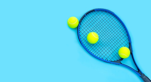 Теннисная ракетка с мячами на синей поверхности