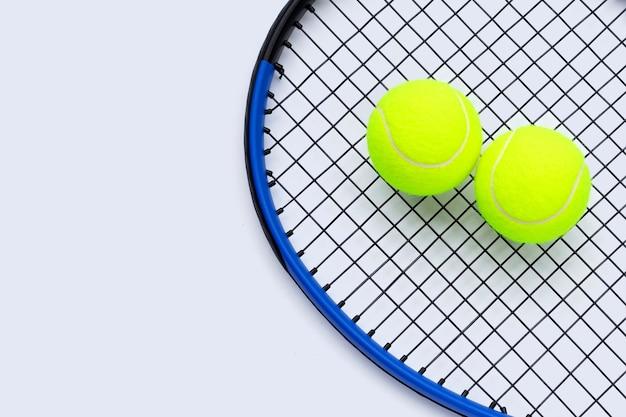 흰색 표면에 공 테니스 라켓