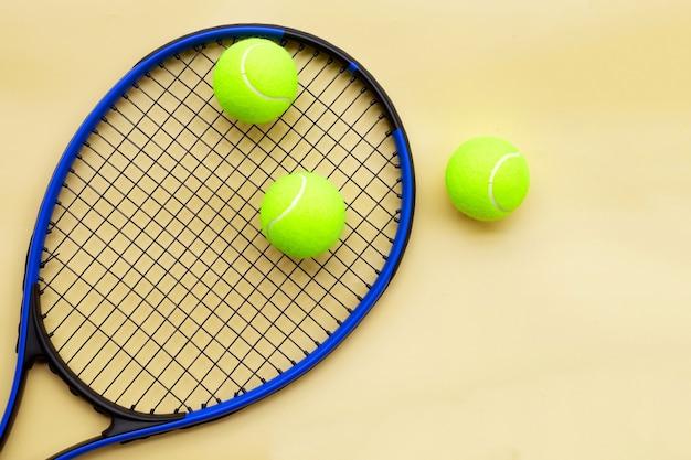 노란색 표면에 공 테니스 라켓