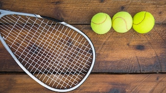 Tennis racket with three balls on wooden textured background