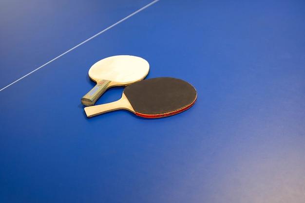 탁구 탁구용 테니스 라켓. 파란색 배경에 장비를 갖춘 탁구대의 세부 사항. 탁구대에 탁구 라켓