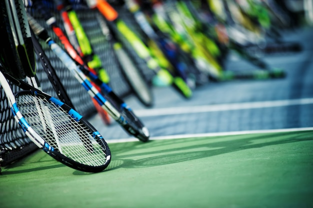 Tennis rackets or tennis racquets leaning against tennis court background