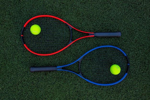緑の芝生の背景にボールとテニスラケット
