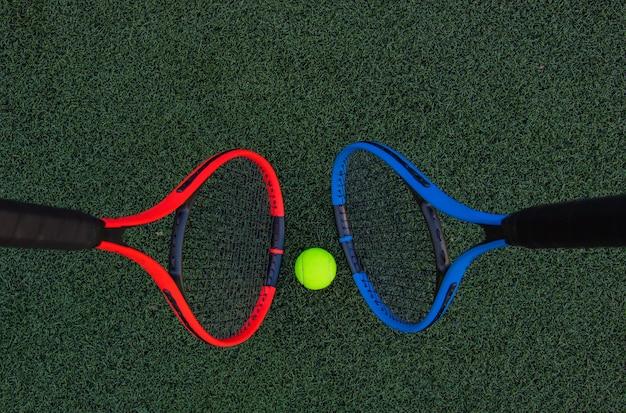 Теннисные ракетки с мячом на фоне зеленой травы