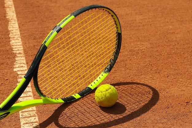 Теннисная ракетка и теннисный мяч на грунтовом корте