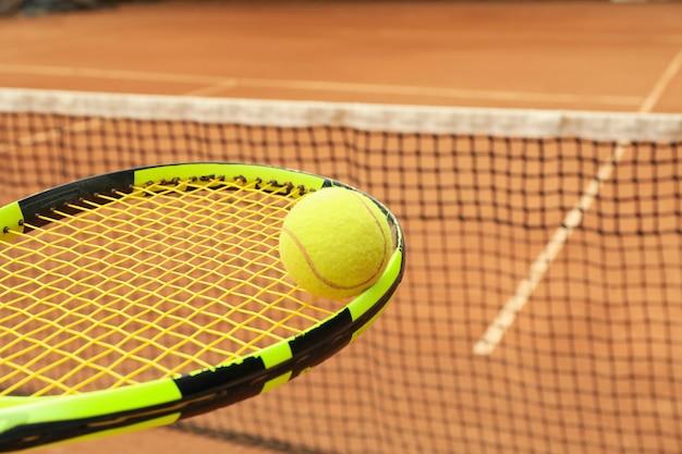 Теннисная ракетка с теннисным мячом против грунтового корта