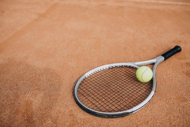 Racchetta da tennis con pallina da tennis che giace in campo