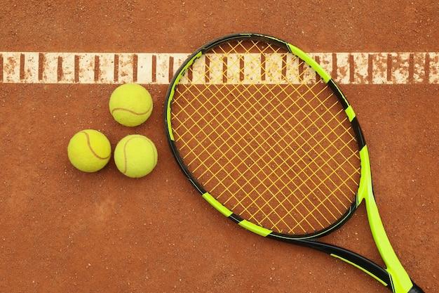 Теннисная ракетка с теннисными мячами на грунтовом корте
