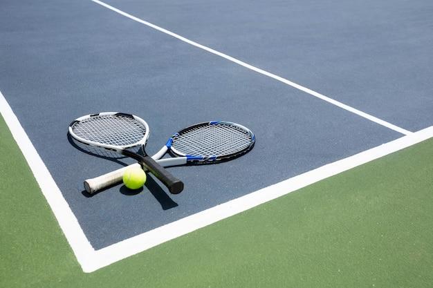 Теннисные ракетки и мяч на корте