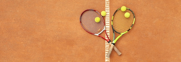 Теннисные ракетки с теннисными мячами на грунтовом корте