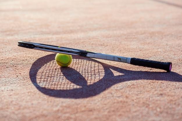Теннисная ракета рядом с теннисным мячом на жестком корте