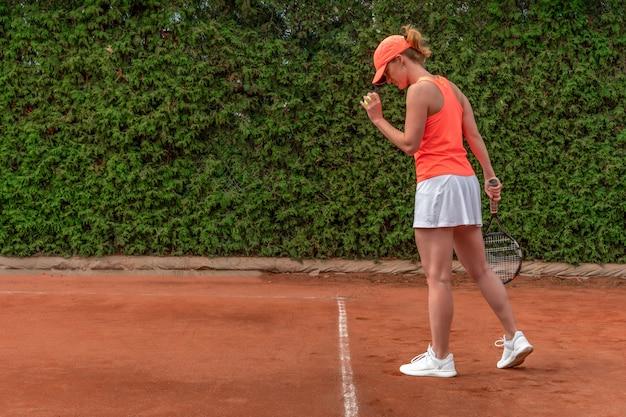 테니스 코트에서 젊은 여자에 의해 서브
