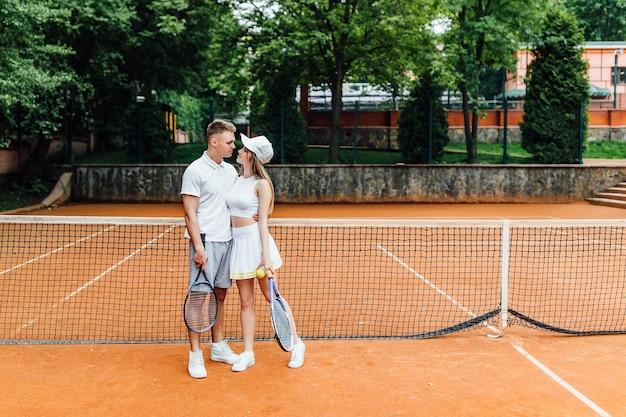 テニススポーツ-夏に外でテニスのゲームをした後にリラックスするカップル。