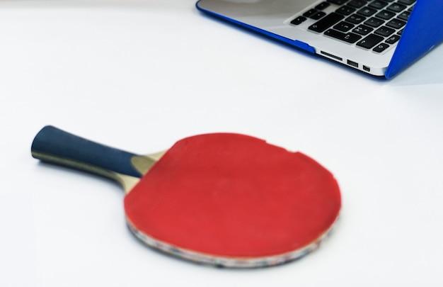Ракетка для настольного тенниса и ноутбук на белом столе