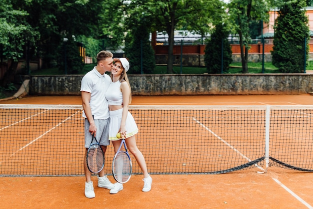 Tennis time, couple relaxing after playing game of tennis outside in summer.