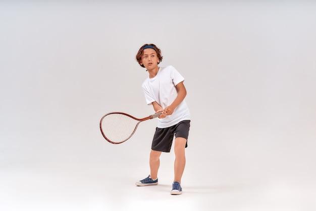 テニスラケットを持って目をそらしている10代の少年のテニストレーニングフルレングスショット