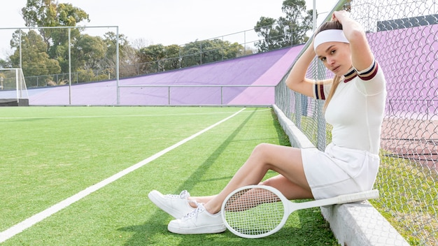 Tennis woman looking at camera while sitting