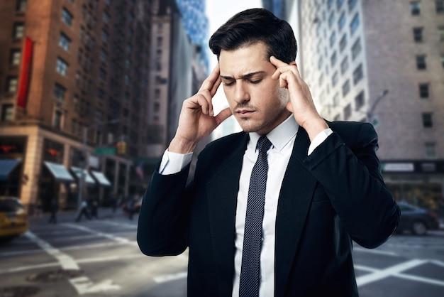 ネクタイと黒のスーツの緊張した思いやりのあるビジネスマンが通り、ビジネスセンターでポーズをとる