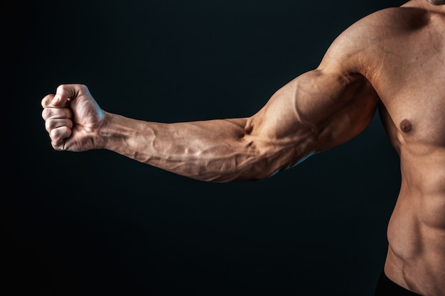 Tense arm clenched into fist, veins, bodybuilder muscles on a dark background, isolate.