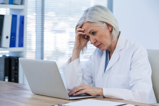 Напряженная женщина-врач работает на своем ноутбуке