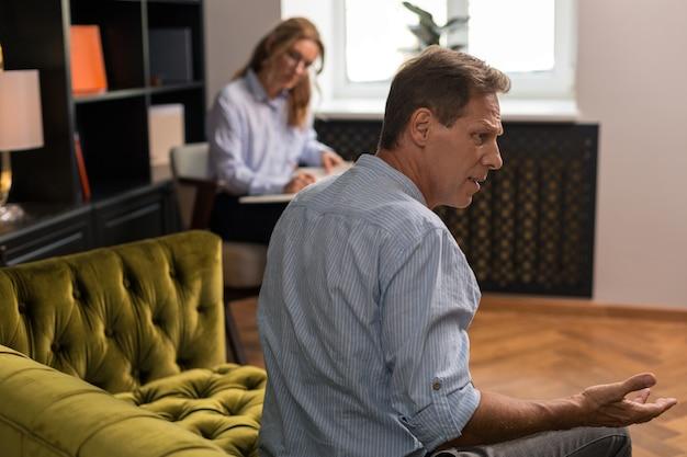 Напряженный мрачный мужчина сидит на оливково-зеленом диване и смотрит вдаль