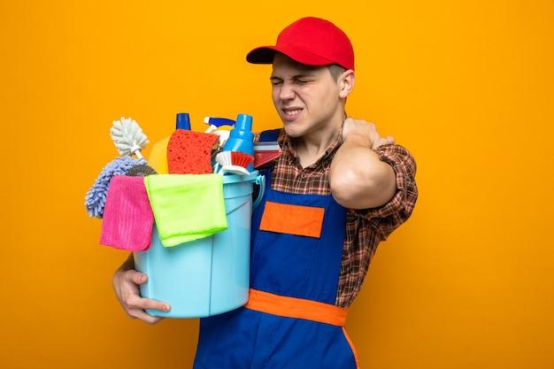 制服と掃除道具のバケツを保持しているキャップを身に着けている緊張したつかんだ首の若い掃除人