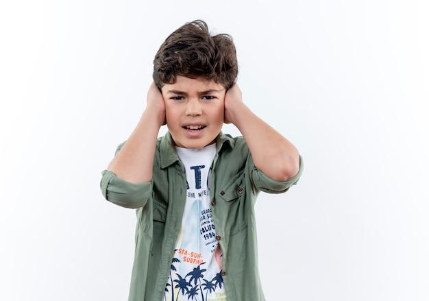 Напряженный маленький школьник закрыл уши, изолированные на белом фоне