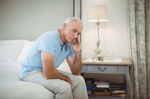 Напряженный старший мужчина сидит на кровати в спальне