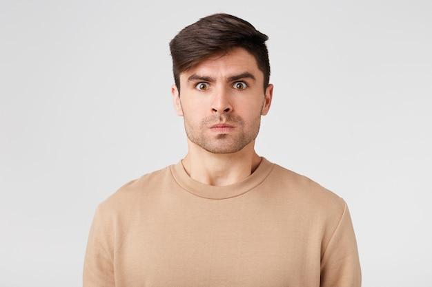 怒りを経験している裸の長袖に身を包んだ緊張した真面目な男