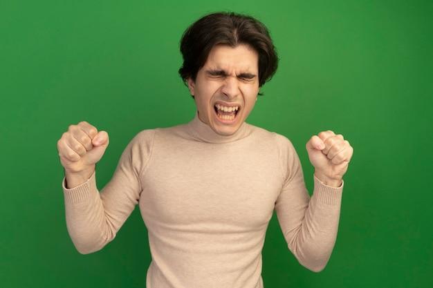 緑の壁に分離された拳を持った目を閉じて緊張する若いハンサムな男