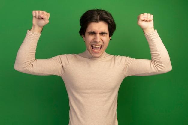 緑の壁に分離された拳を上げる目を閉じて若いハンサムな男の緊張