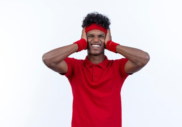 머리띠와 팔찌를 착용하는 긴장된 젊은 아프리카 계 미국인 스포티 한 남자는 흰색에 고립 된 귀를 폐쇄