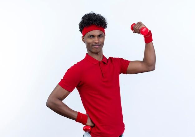Напряженный молодой афро-американский спортивный мужчина с повязкой на голову и браслет, поднимающий гантели, изолированные на белом