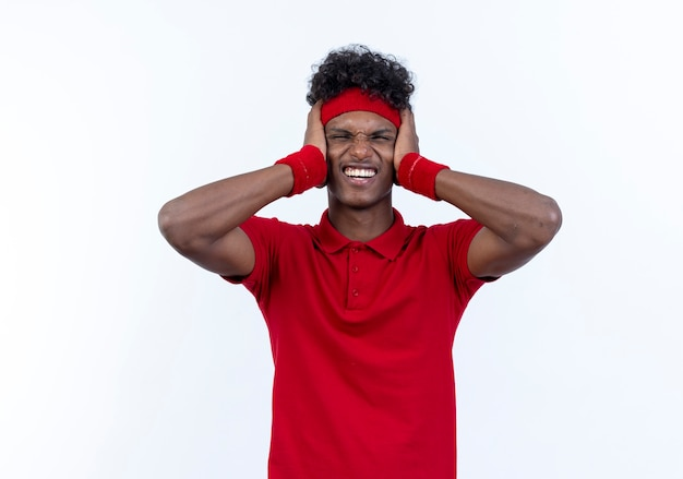Teso giovane afro-americano sportivo che indossa la fascia e il braccialetto chiuso le orecchie isolate su bianco