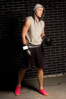 彼の戦いを待っている緊張した若いボクサー